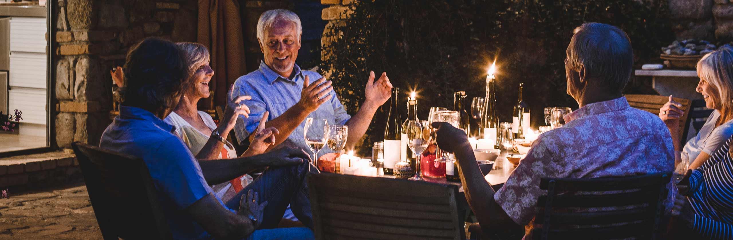 Persone riunite attorno a un tavolo mentre cenano all'aperto