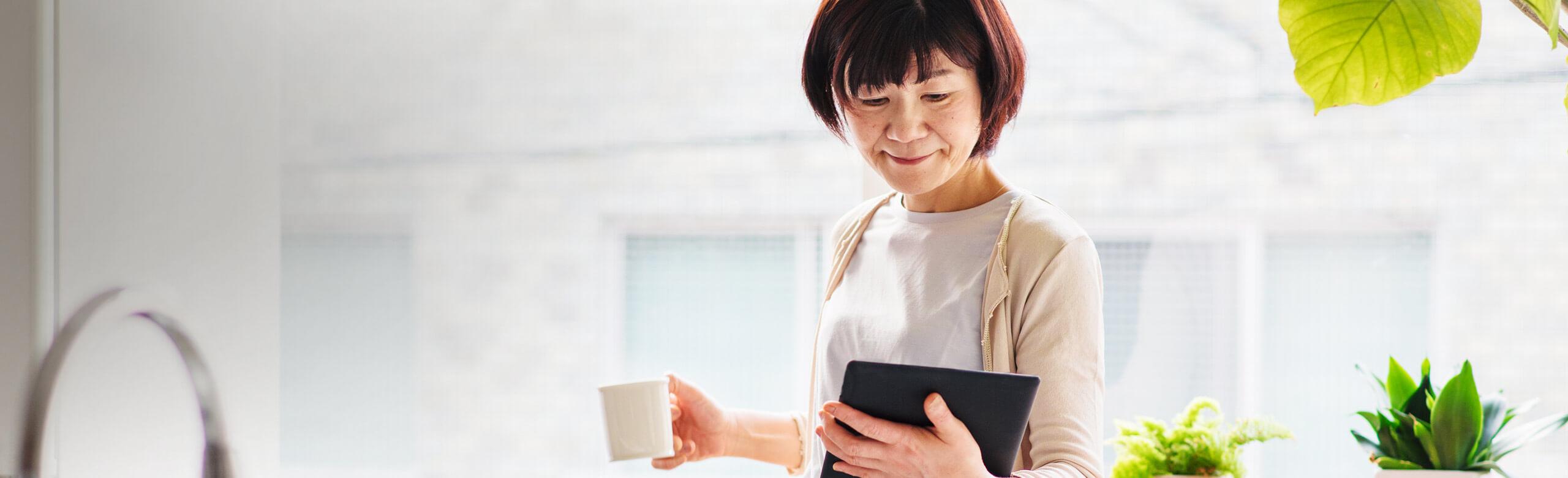 Una donna tiene in mano una tazza di caffè e un tablet
