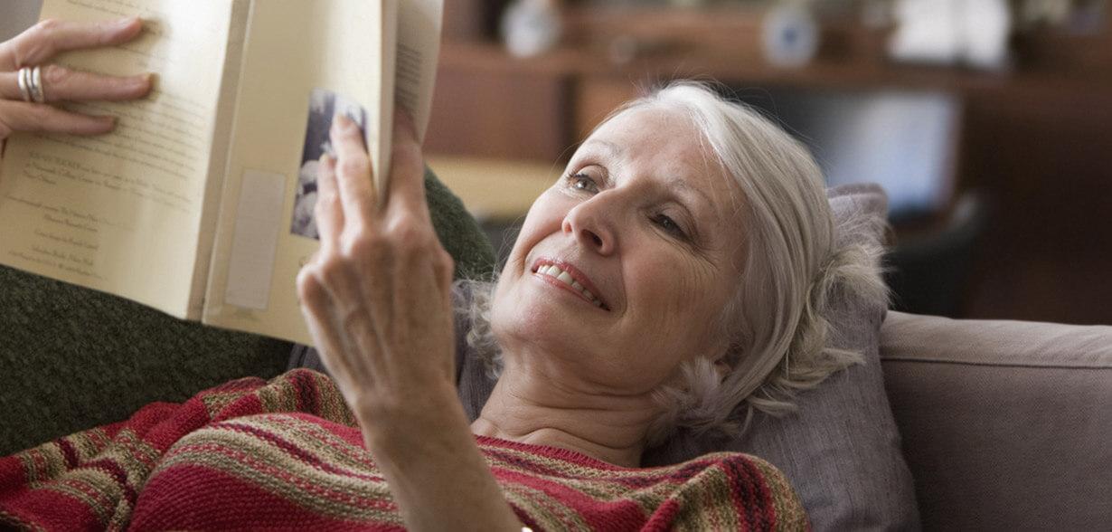 Una donna stesa sul divano mentre legge un libro