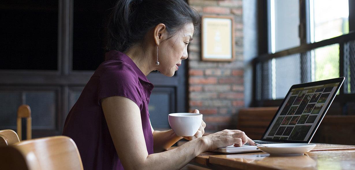 Una donna mentre beve un caffè e lavora al computer portatile
