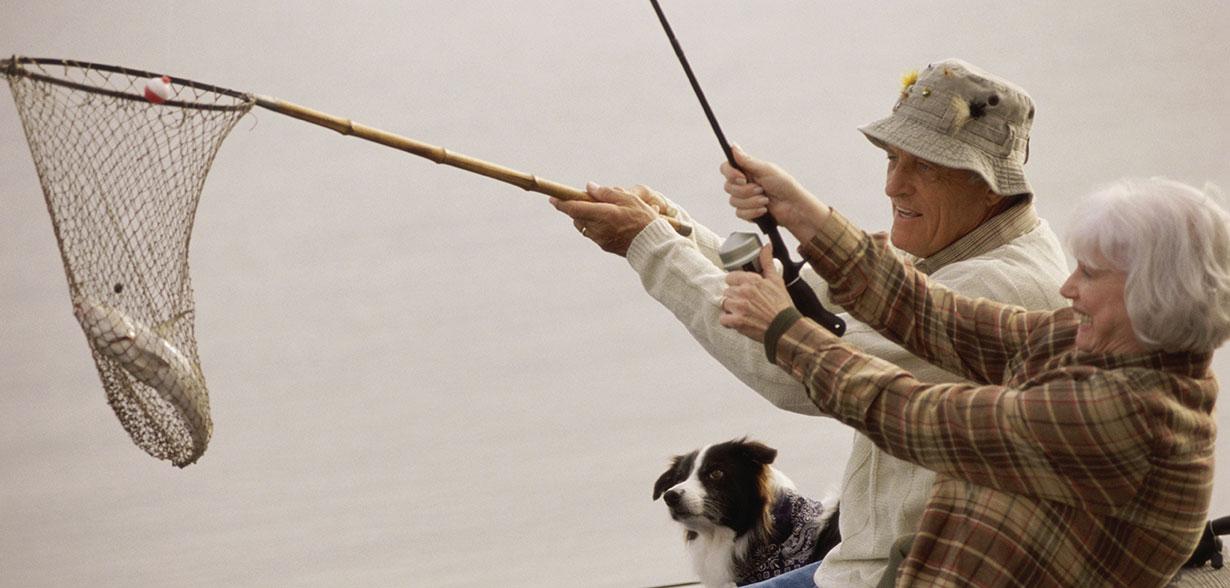 Coppia di anziani che pescano con una rete e una canna da pesca